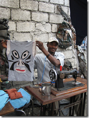 Tailor Jonas La Base with the project's first completed garment, Port-au-Prince, 2009; photo credit Carole Frances Lung