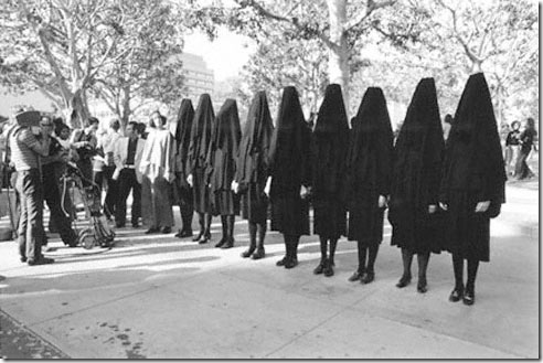 In Mourning and in Rage (1977) by California artist Suzanne Lacy (now recognised as a distinct politically relevant  performance art 'school of thought', out of the West Coast of North America). Protestors are in robes and hoods; this isperformance art using textile arts (costuming) as a social-change activist strategy, to protest against the murders and rapes of ten random women in Los Angeles.